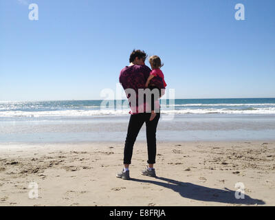 Rear view of mother holding her daughter (18-23 months) on the beach and looking at sea - Stock Photo