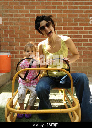 Mother and daughter (18-23 months) driving cart - Stock Photo