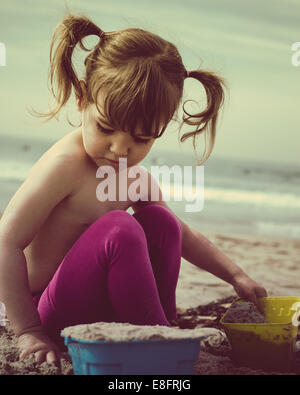 Girl (18-23 months) building sand castle on beach - Stock Photo