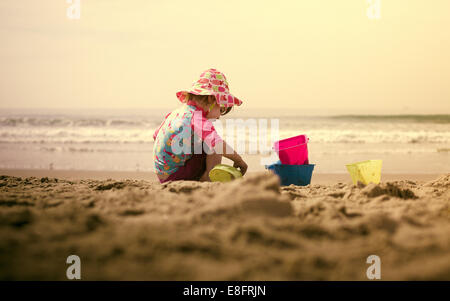 Girl (18-23 months) playing in sand on beach - Stock Photo