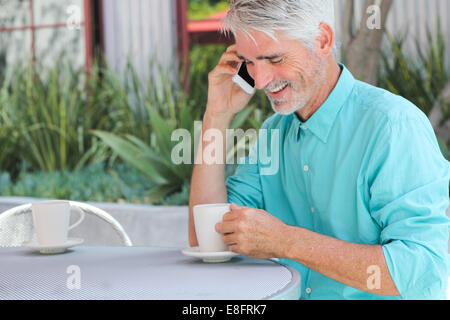 Businessman having cup of coffee while talking on phone - Stock Photo