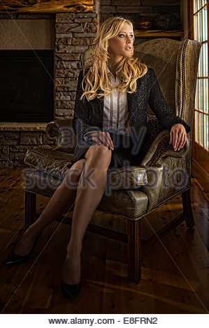 thoughtful businesswoman sitting with legs crossed on