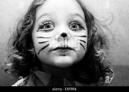 Portrait of girl (4-5) with cat face paint - Stock Photo
