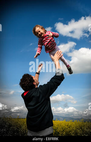Father standing in a field throwing his daughter in the air - Stock Photo