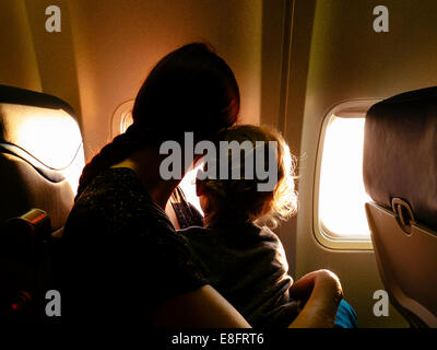 Mother and son looking out of airplane window - Stock Photo