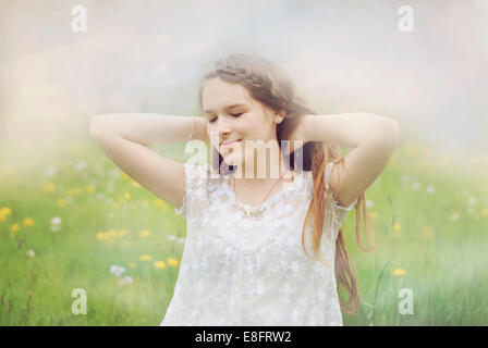Portrait of a beautiful girl standing in a meadow - Stock Photo