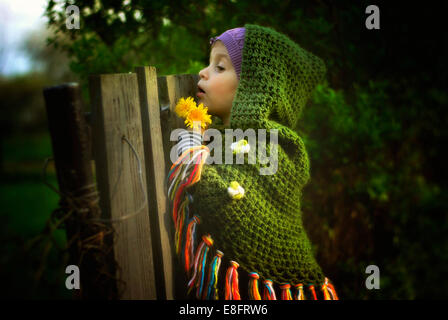 Young girl looking over fence - Stock Photo