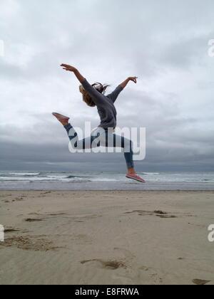 USA, Oregon, Tillamook County, Rockaway Beach, Young woman practicing ballet on beach
