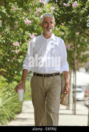 Businessman walking down street - Stock Photo