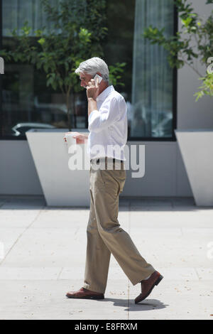 Side view of businessman walking down street while talking on mobile phone - Stock Photo
