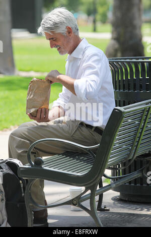 Businessman sitting on bench in park with his lunch - Stock Photo