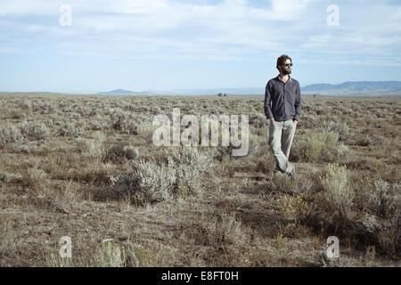 USA, Man standing in sagebrush - Stock Photo