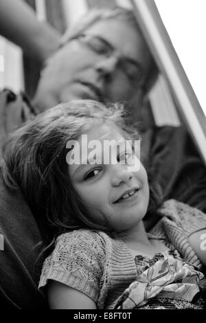 Portrait of a girl leaning against sleeping father - Stock Photo