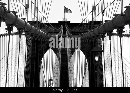 USA, New York City, Manhattan, Close up of Brooklyn Bridge with flag - Stock Photo