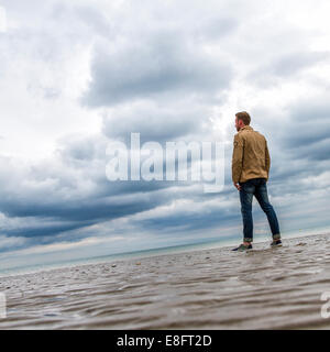 Man on beach looking at view - Stock Photo