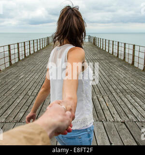 UK, Woman holing man's hand on pier - Stock Photo