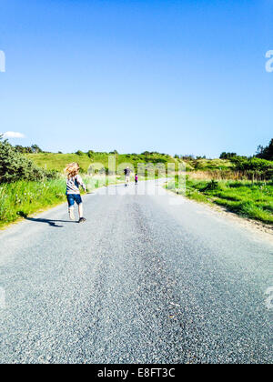 Rear view of Man running down road with two sons, Denmark - Stock Photo