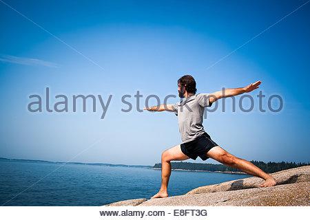 Man doing warrior yoga pose on beach, Maine, America, USA - Stock Photo