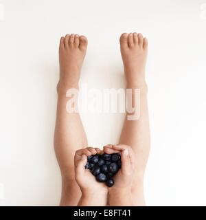 Boy holding blueberries in his hands - Stock Photo