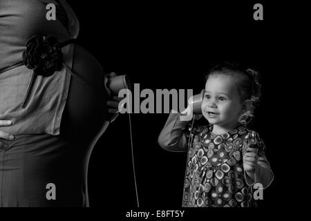 Girl listening to her pregnant mother's abdomen with a toy string phone - Stock Photo