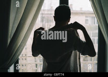 Man standing in front of a window getting dressed - Stock Photo