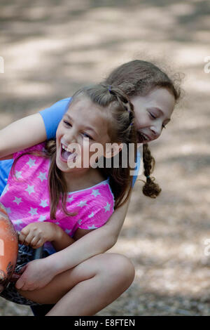 Two girls sitting on a seesaw in the playground - Stock Photo