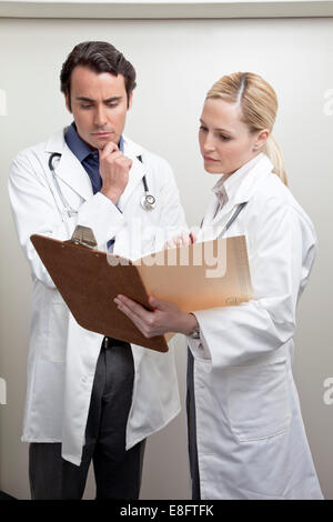 Male and female doctor looking at a medical chart - Stock Photo