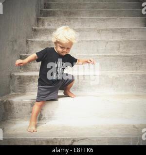 boy walking down steps - Stock Photo