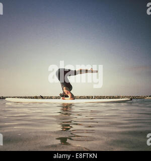 Woman doing a supported yoga headstand on a paddleboard, california, america, USA - Stock Photo