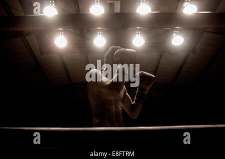 Boxer in a boxing ring with hands raised in front of his face - Stock Photo