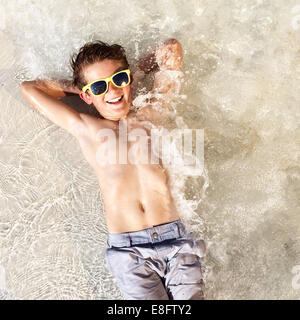 Overhead view of smiling boy lying in shallow sea with hands behind head - Stock Photo