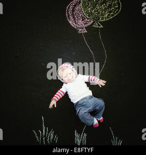 Baby boy with chalk drawing of balloons - Stock Photo