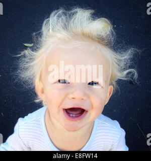 Portrait of a laughing boy with windswept hair - Stock Photo