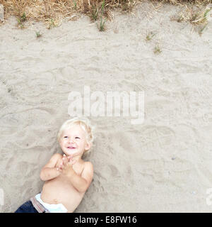 Overhead view of boy lying on beach - Stock Photo