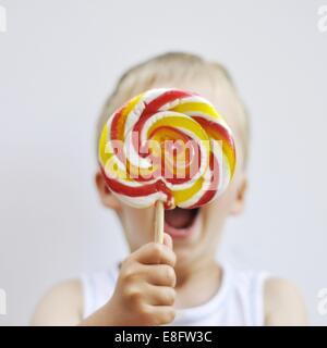 Boy holding a giant lollipop - Stock Photo