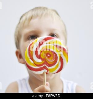 Boy licking a giant lollipop - Stock Photo