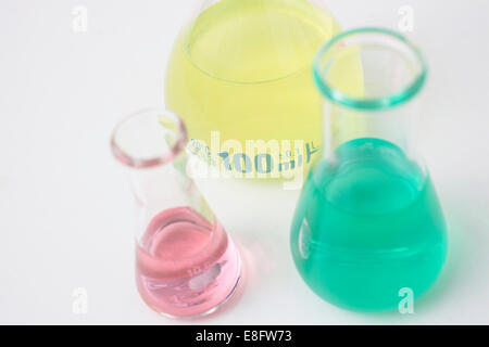 Three conical flasks and measuring beakers in research laboratory - Stock Photo