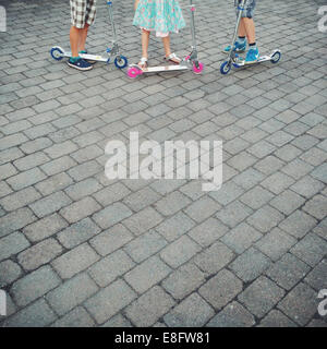 Close up of children (10-11, 12-13) standing next to scooters - Stock Photo