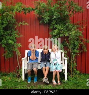 Three children (10-11, 12-13) sitting on bench in garden - Stock Photo