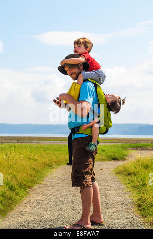 Father carrying his son and daughter, USA - Stock Photo