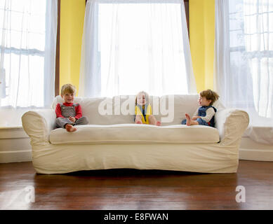 Three children sitting on a sofa in the living room
