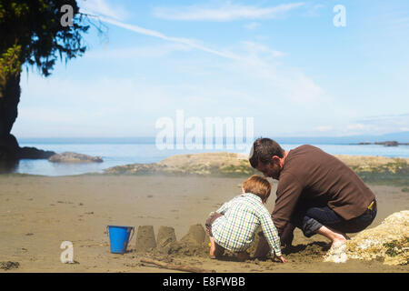 Father and son building a sandcastle on the beach, USA - Stock Photo