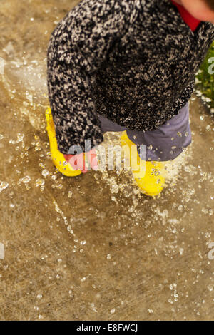 Boy walking through puddle (2-3 years) - Stock Photo