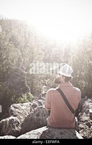 USA, Wyoming, Man sitting on rocks above trees - Stock Photo