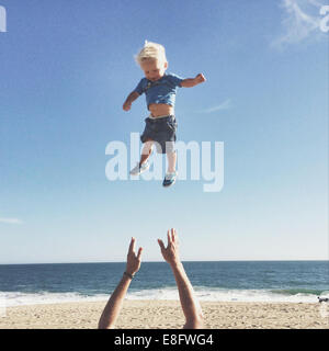 Father throwing son up in air - Stock Photo