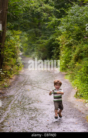 Boy (2-3) playing in woods - Stock Photo
