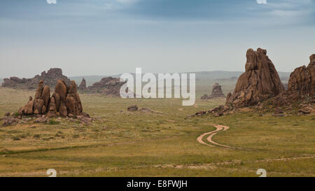 Dirt track between rock formations in field - Stock Photo