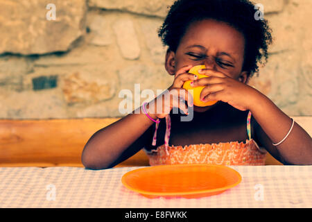 Girl sitting at a table eating an orange - Stock Photo