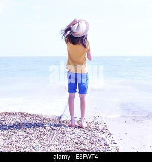 Rear view of girl standing on beach holding hat - Stock Photo