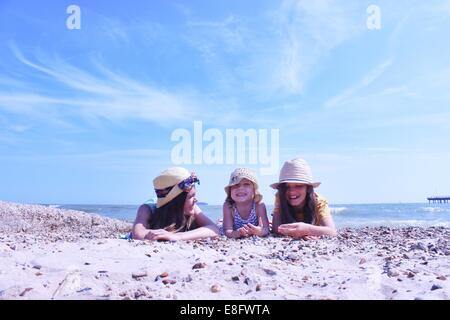 Three Girls on beach lying on their front - Stock Photo